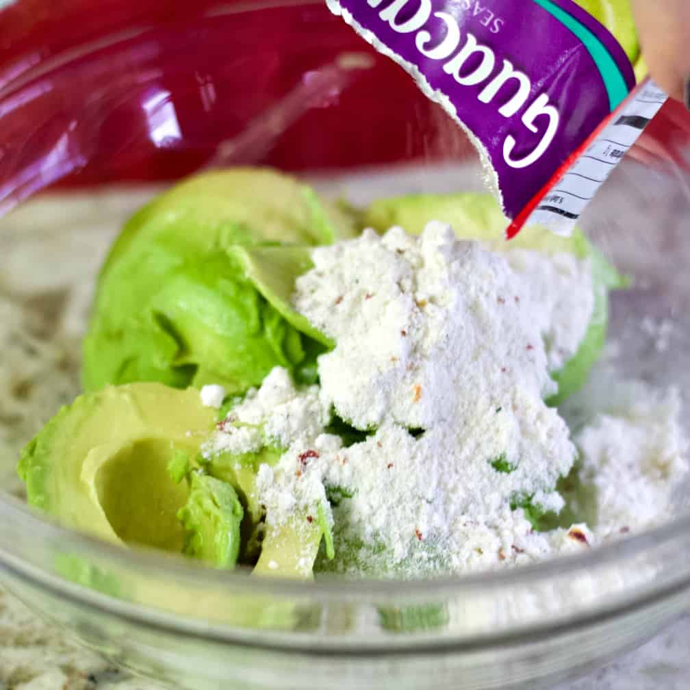 Adding the guacamole seasoning to avocado-layered bean dip.