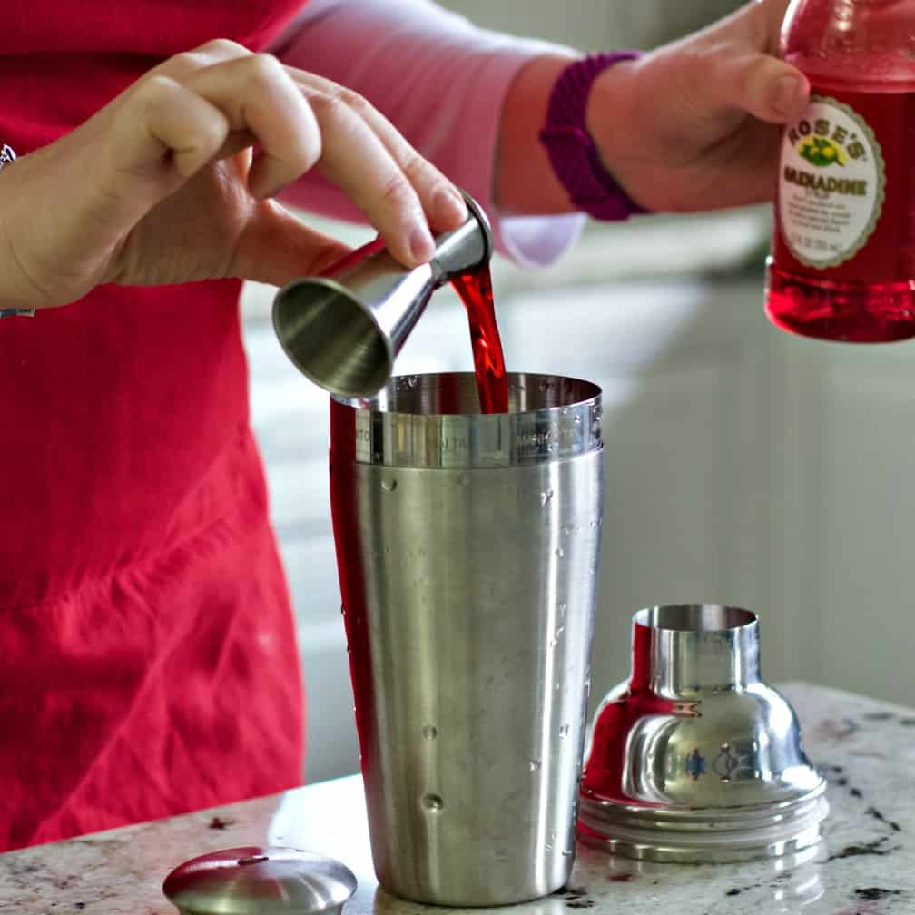 pouring grenadine into shaker.