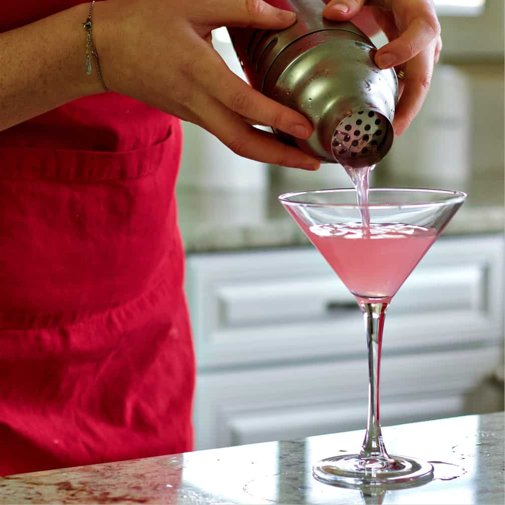 strain the cosmopolitan drink from the shaker