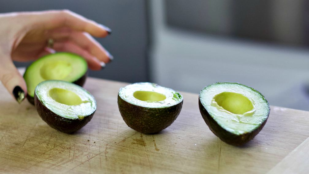 avocado halves on a wooden board.