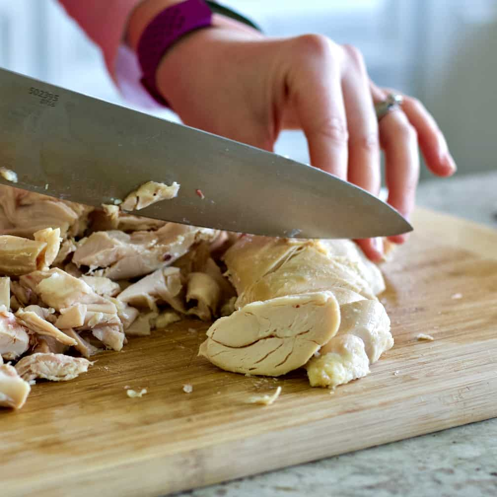 chopping rotisserie chicken meat into bite sized pieces-chicken soup recipe