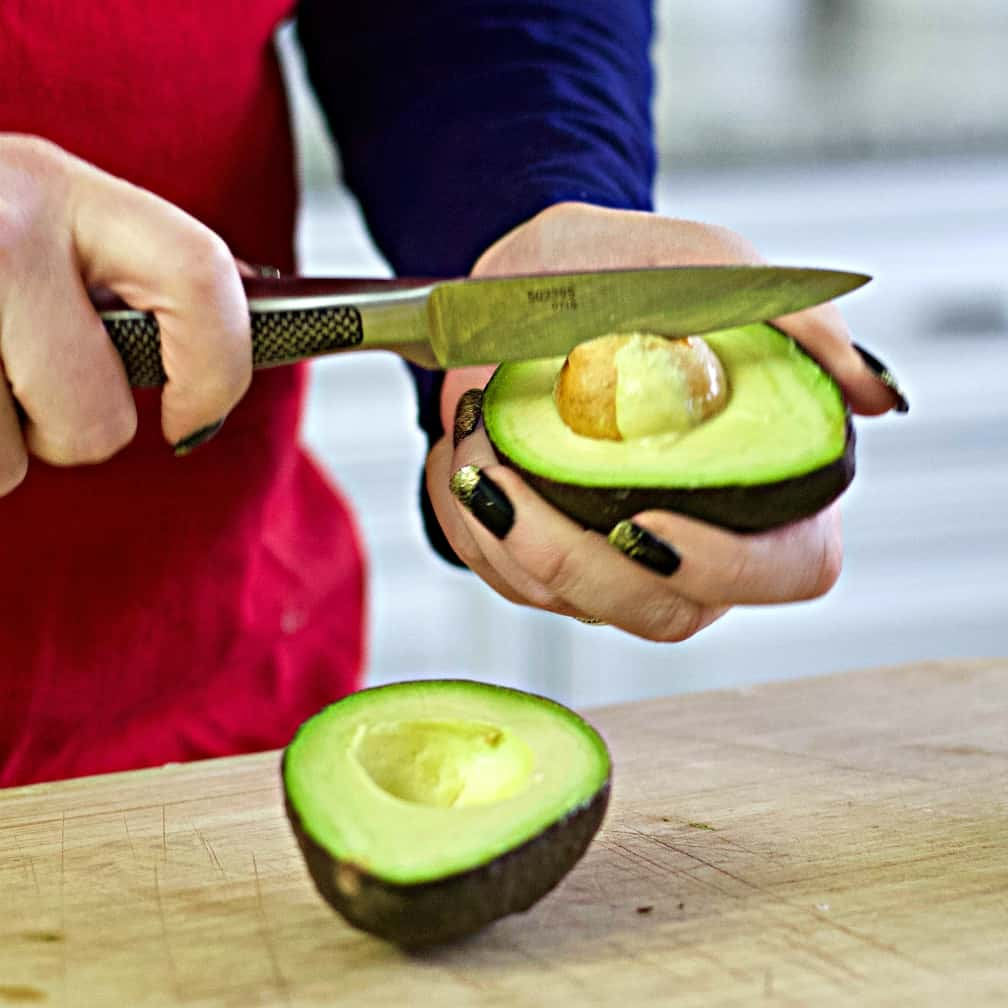 pPitting avocados with a knife- layered bean dip