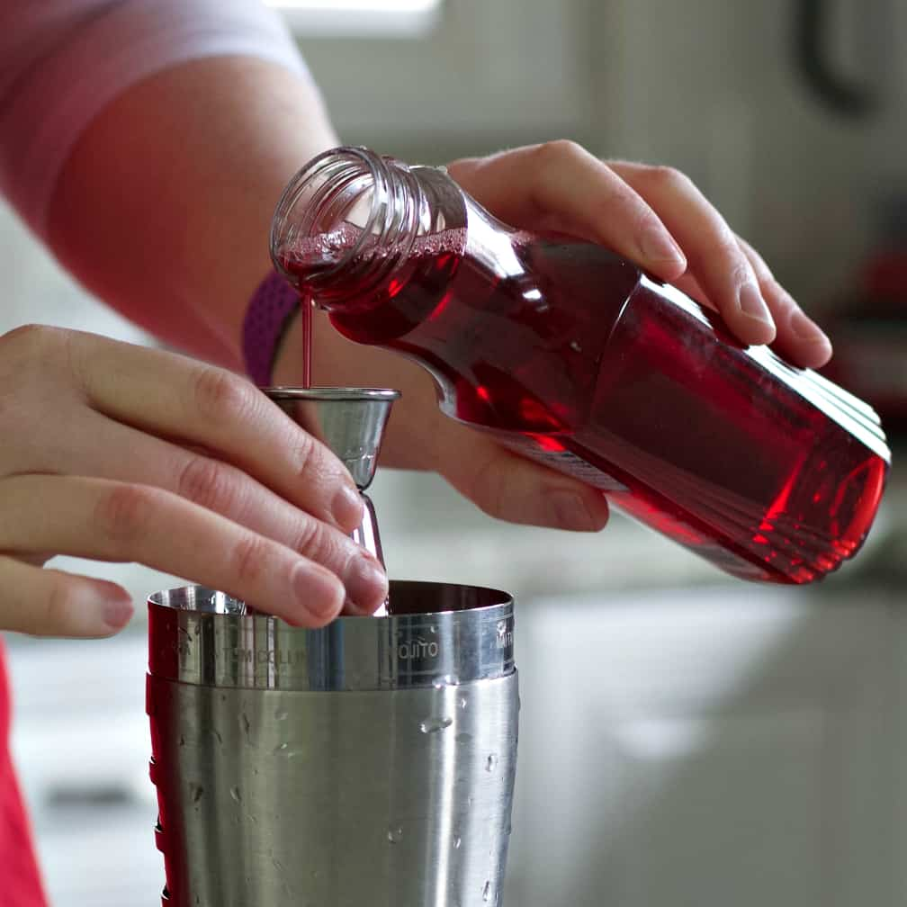 pouring grenadine for a Cosmopolitan drink