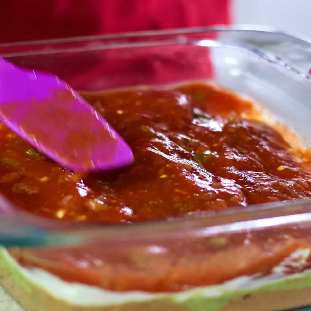 smoothing salsa over sour cream