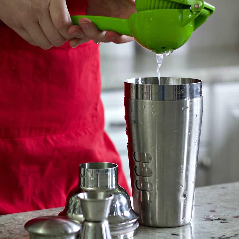 squeezing lemon juice into shaker