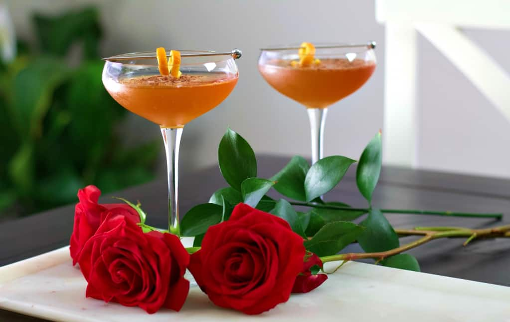 two chocolate orange margaritas on a white tray with red roses.
