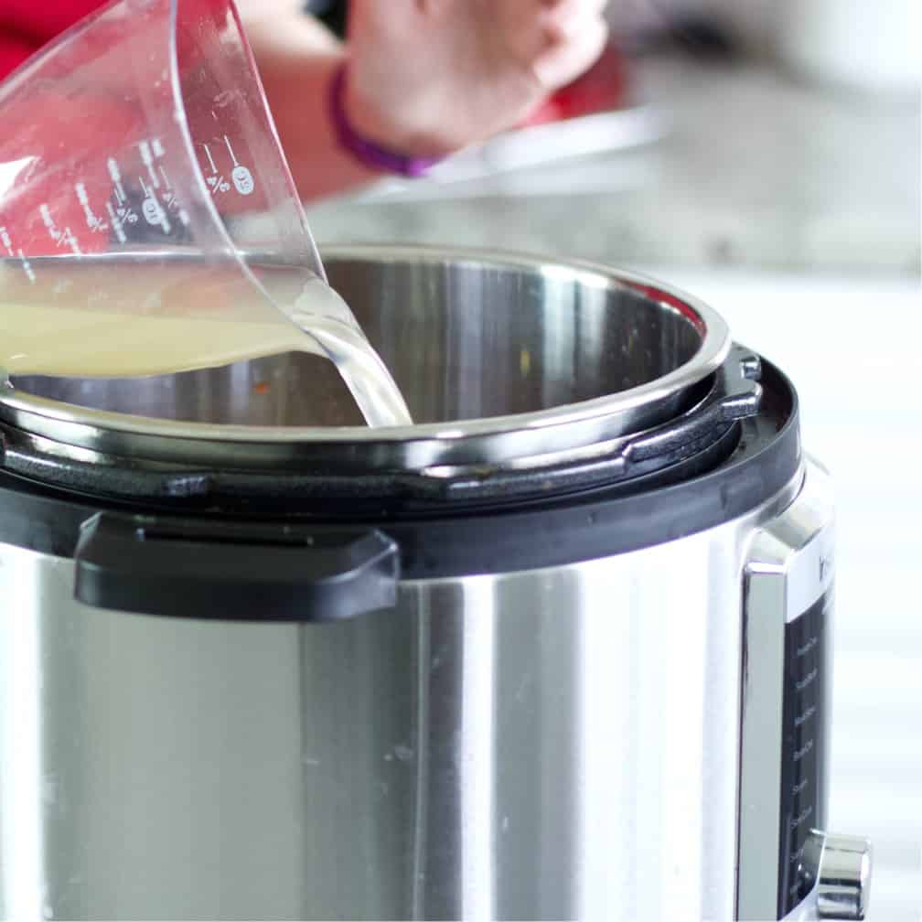 pouring chicken broth-chicken chili
