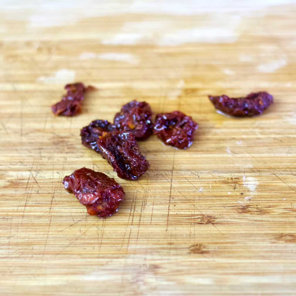 sun dried tomatoes on a wooden cutting board.
