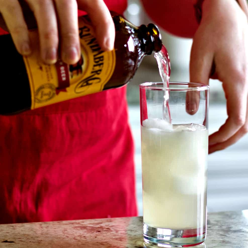 pouring ginger beer into Mezcal cocktail