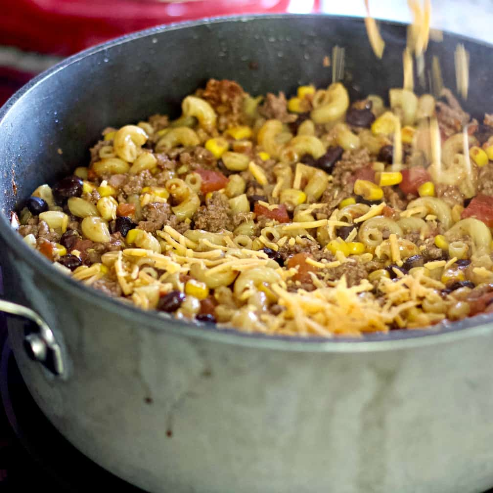 Sprinkling cheese over chili mac