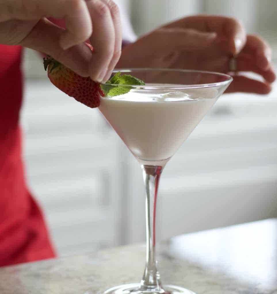 garnishing strawberries and cream cocktail