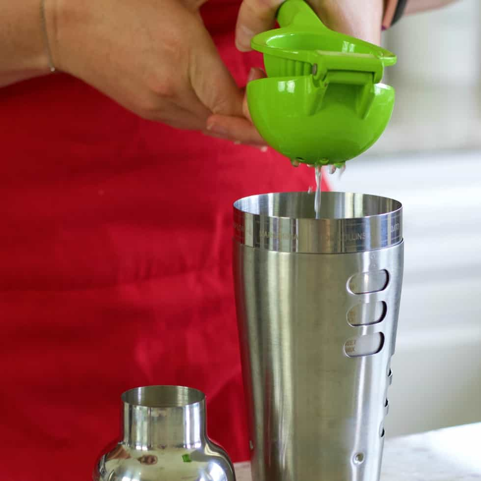 squeezing a lime-blue margarita recipe