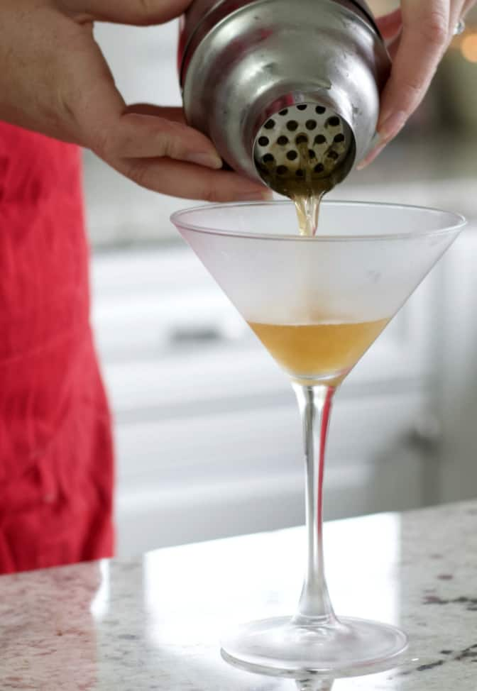 pouring banana split cocktail into chilled martini glass