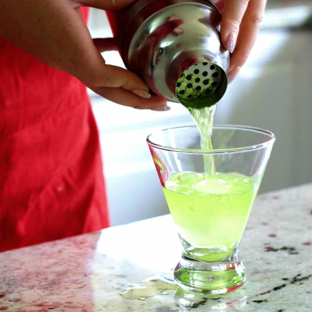 Straining Midori Sour Into Glass