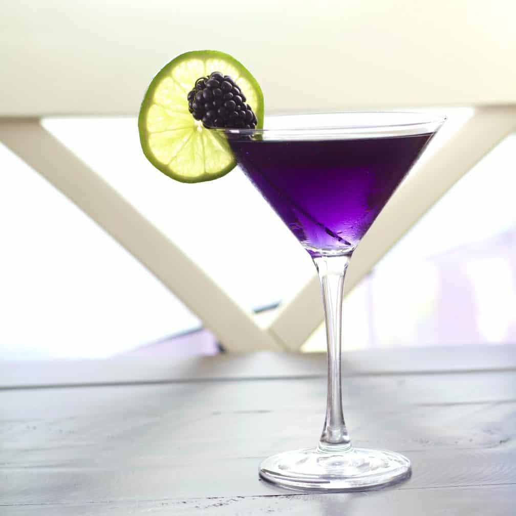 purple rain drink with a lime wheel