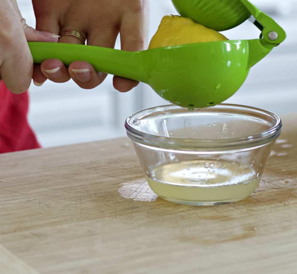 squeezing fresh lemon-lemon butter sauce