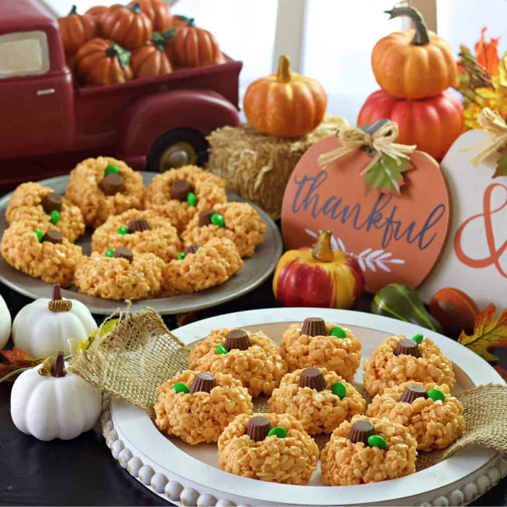 pumpkin rice krispie treats on white and metal trays on themed table
