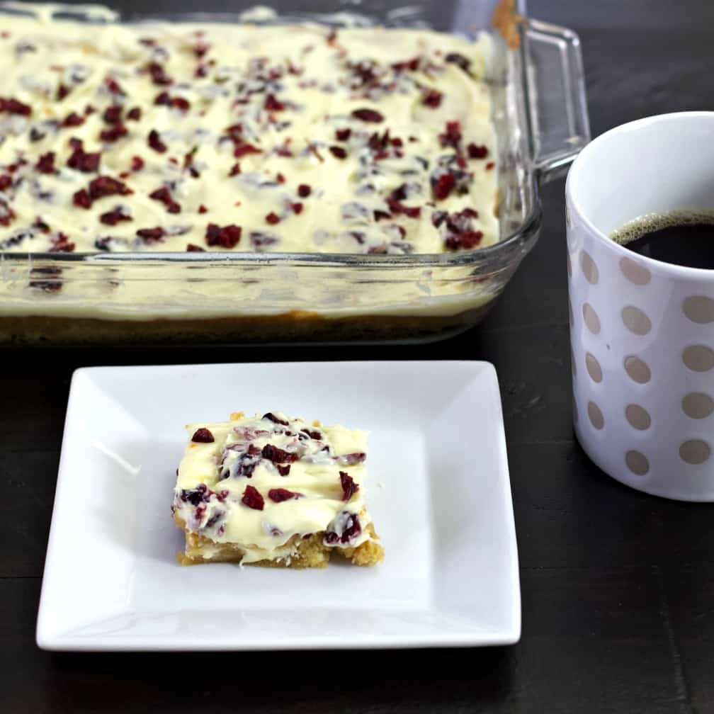 cranberry bliss bar with coffee and panful
