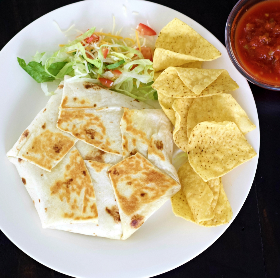 Crunchwrap supreme top shot with tortilla chips and salsa