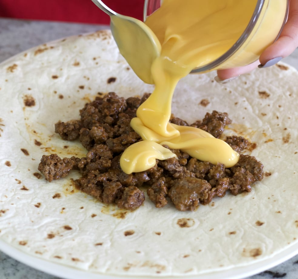 pouring on cheese sauce
