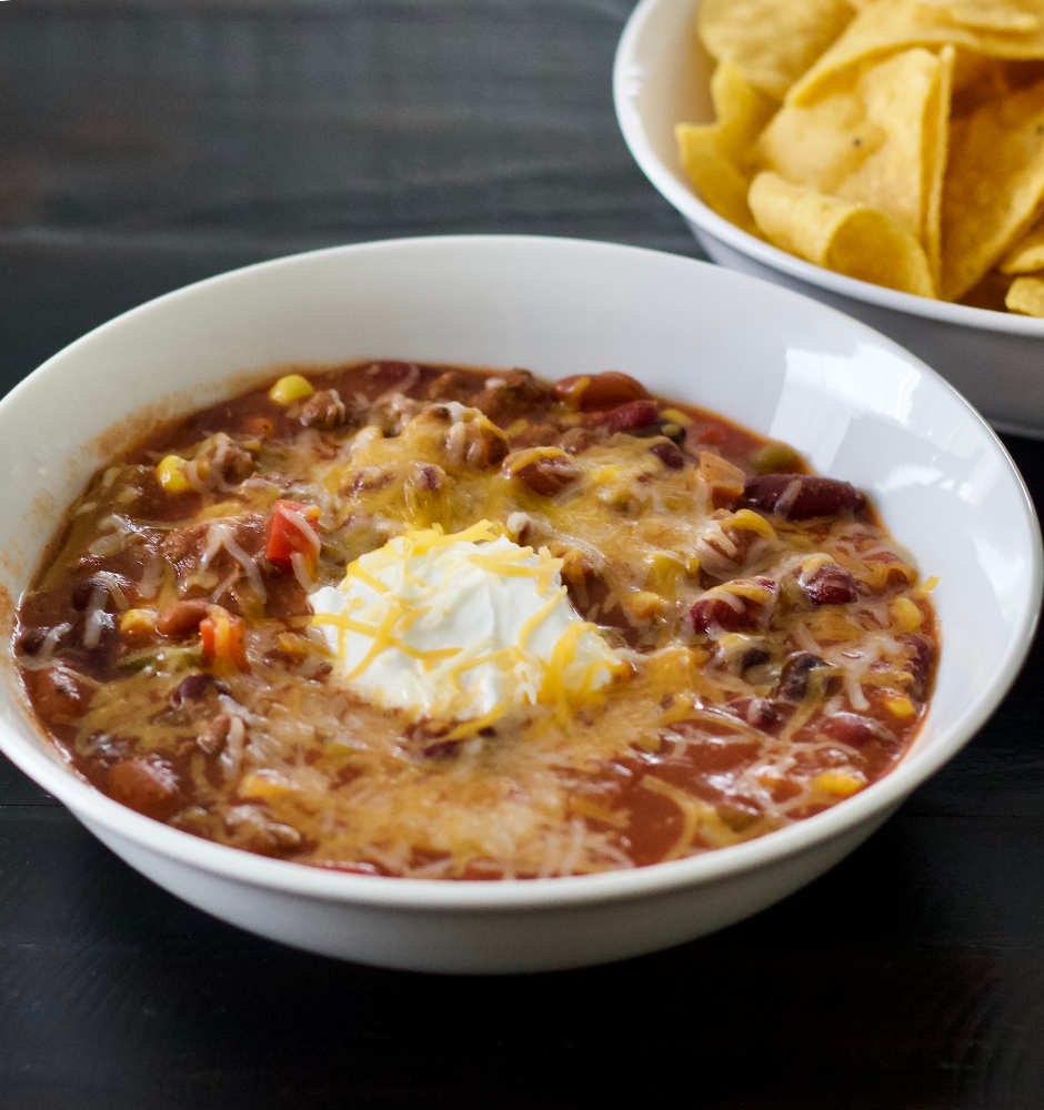 chili with sour cream and cheddar cheese on top. Served with tortilla chips