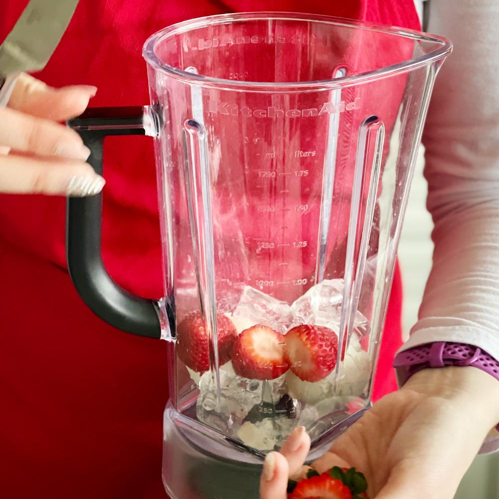 adding cut strawberries into blender