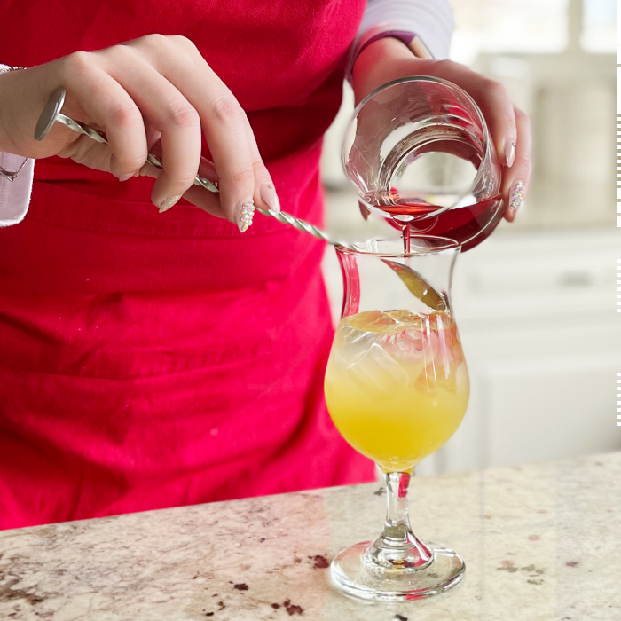 Pouring cranberry juice over back of spoon-layering