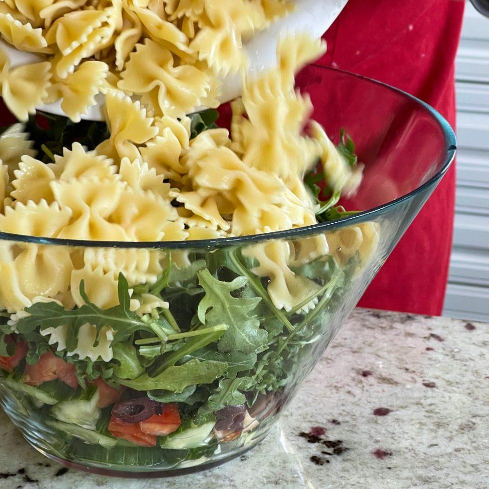 adding pasta to Mediterranean salad