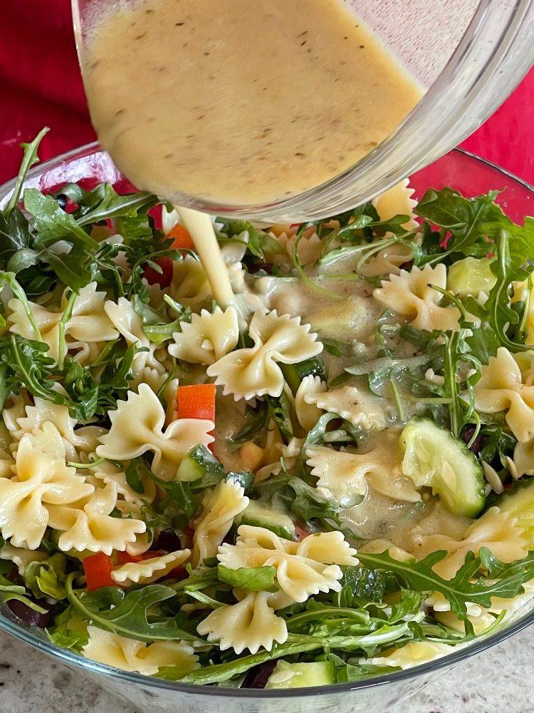 pouring Greek Dressing over Mediterranean salad