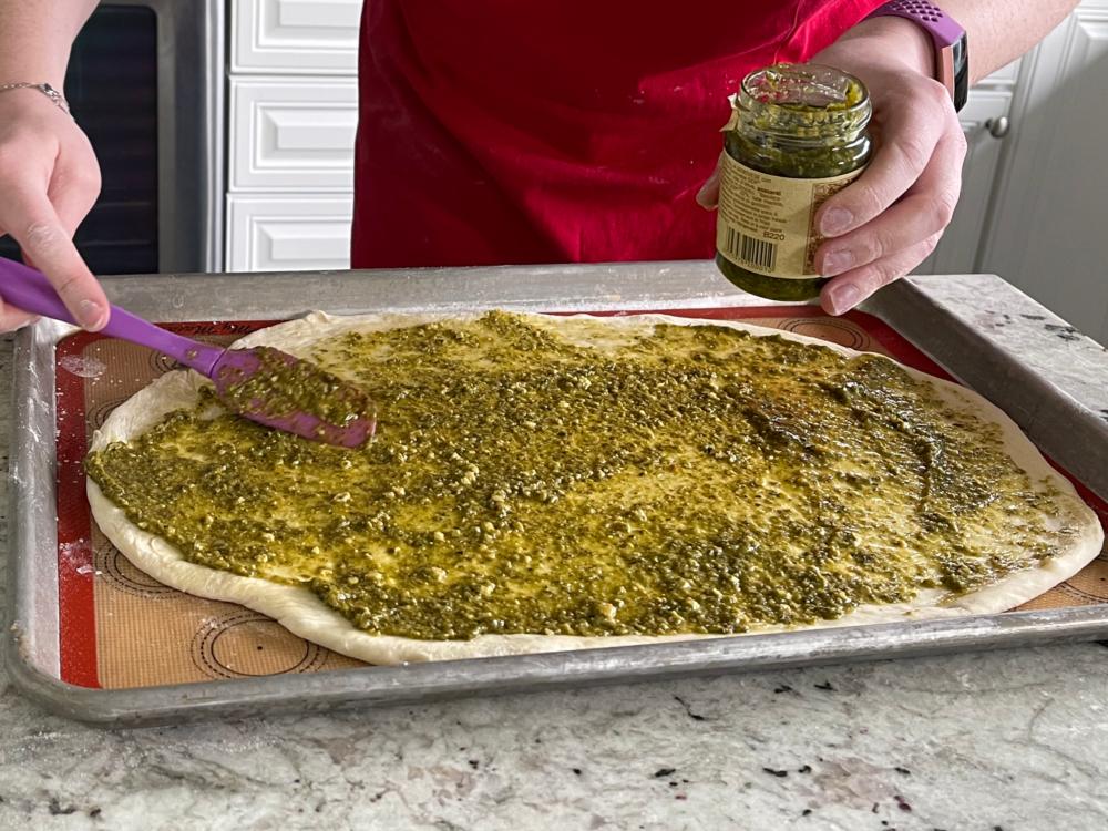 spreading pesto on flatbread