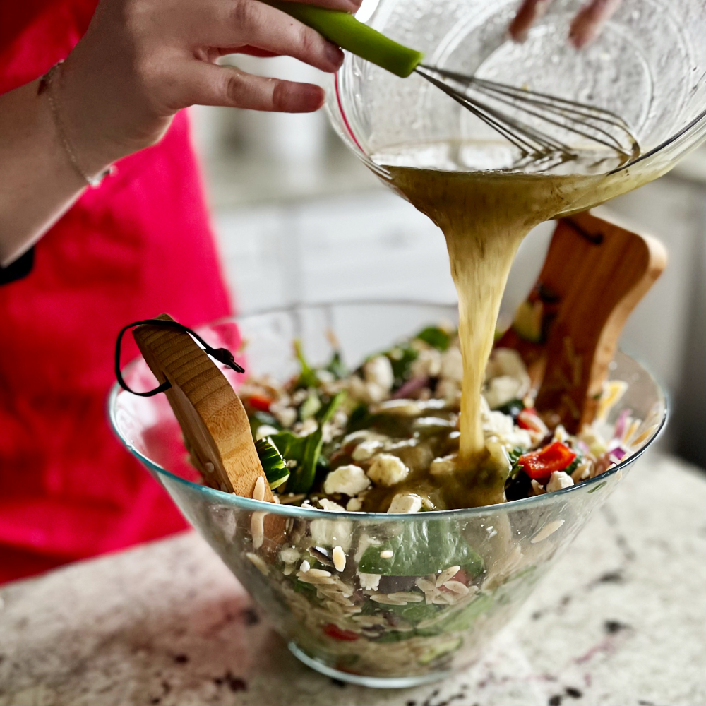 pouring dressing on orzo salad