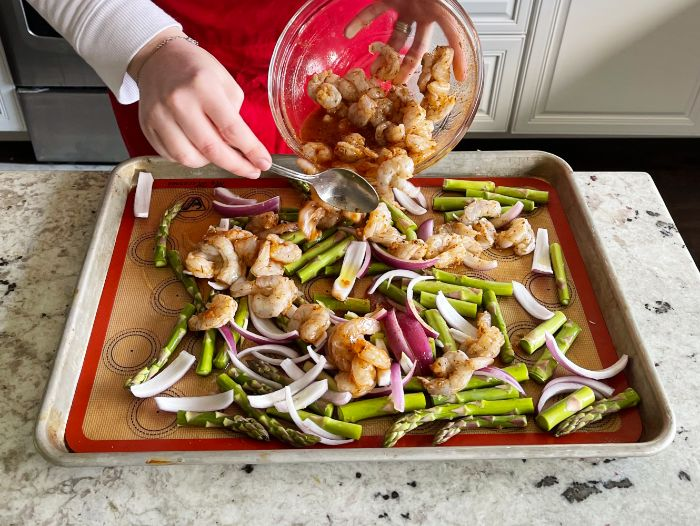 spooning shrimp over veggies on sheet pan