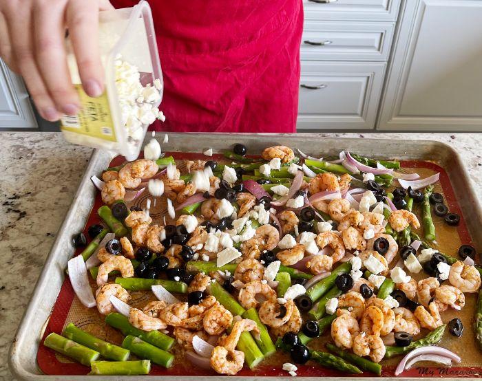 sprinkling Feta over shrimp dinner