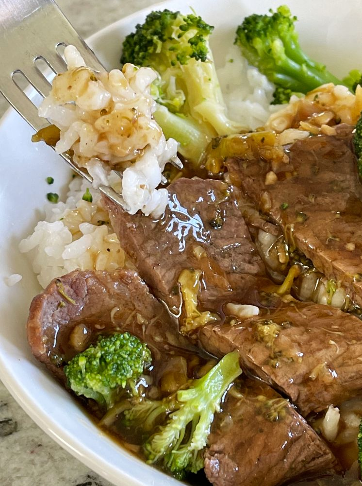 forkful of rice with asian sauce beef and broccoli dinner