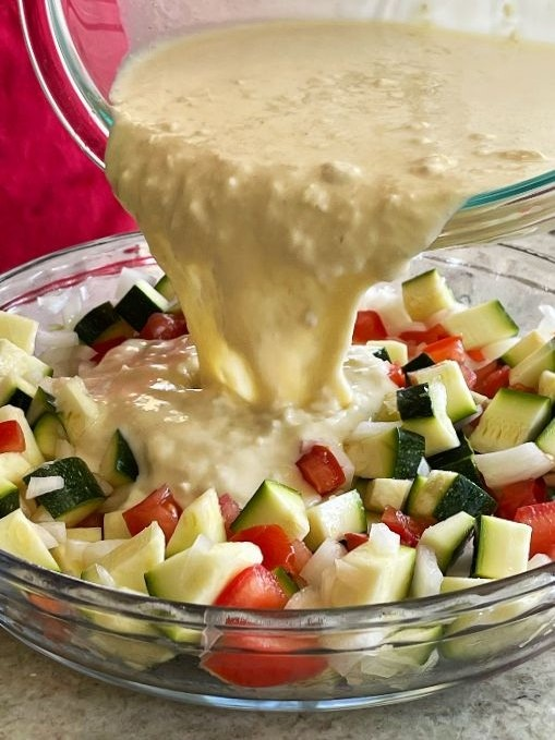 pouring bisquick batter into vegetables-zucchini pie