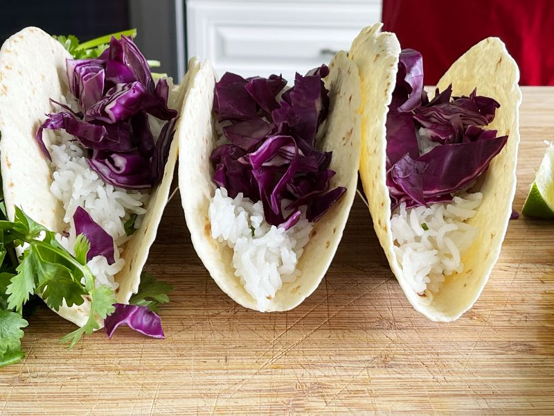 adding red cabbage to taco